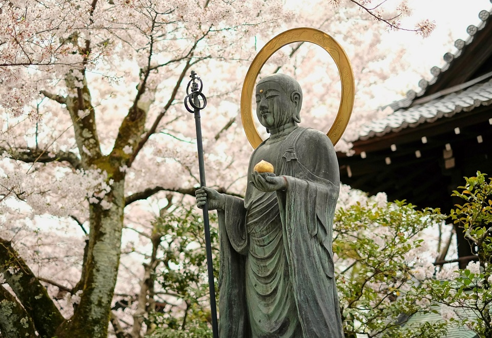 Kyoto's Finest: Cherry Blossom Season - EYExplore - A Buddhist statue surrounded by cherry blossoms just south of Maruyama Park.