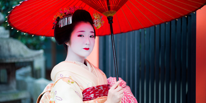 A lovely geisha poses in a garden while holding her iconic red umbrella