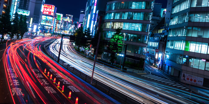 Long exposure photo of traffic streaming through Shinjuku with neon lights in the distance