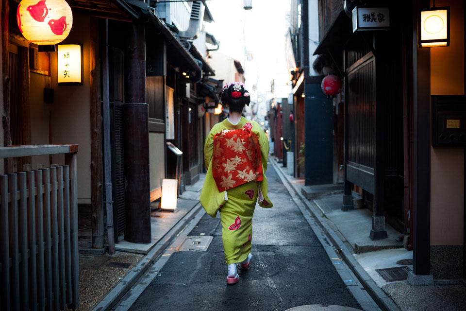 A geisha clad in a green Kimono walks through Pontocho, Kyoto - EYExplore